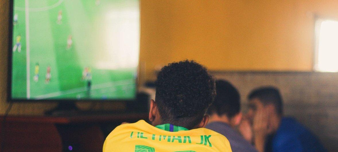 Young men in Volta Redonda, Brazil, watch a soccer match on TV.