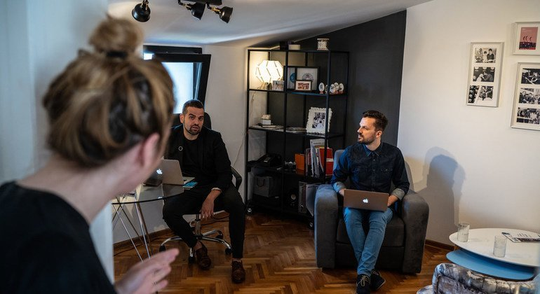 Darko speaks with some of his colleagues at the offices of his communications firm in Belgrade, Serbia.