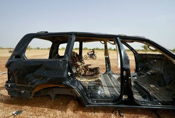 A man on a motorcycle drives by a burnt-out car in the northern region of Burkina Faso where security incidences continue to rise. (June 2019)
