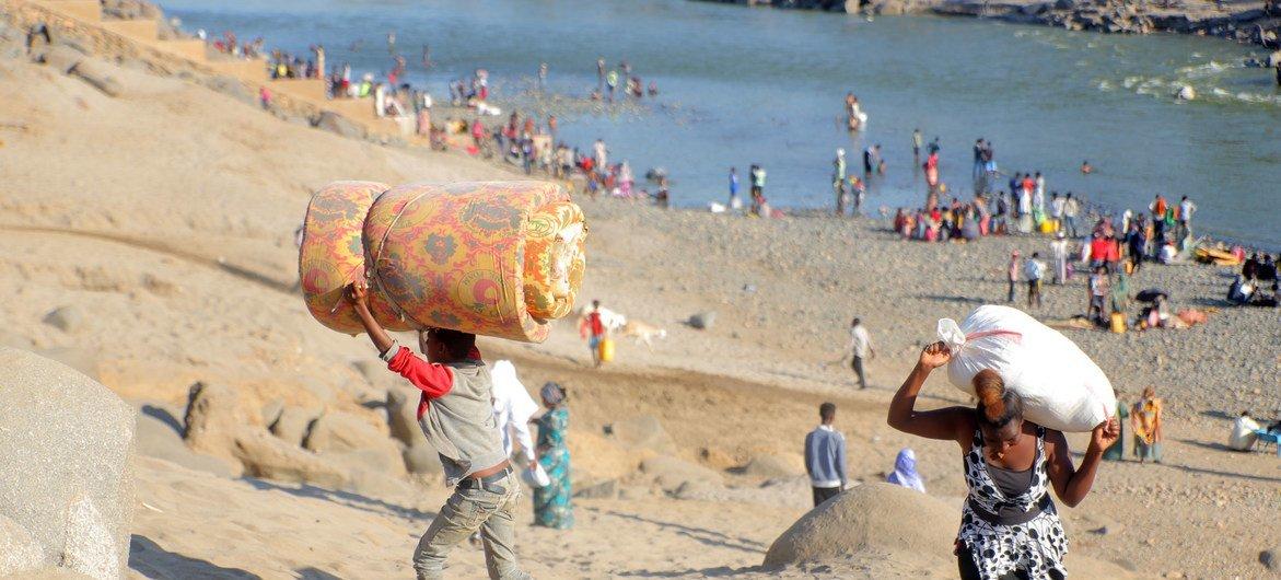 Refugiados etíopes fogem de confrontos na região de Tigray atravessando o rio Tekeze em Hamdayet, Sudão.
