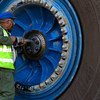 A worker repairs a wheel of a giant haul truck at a uranium mine in Namibia.