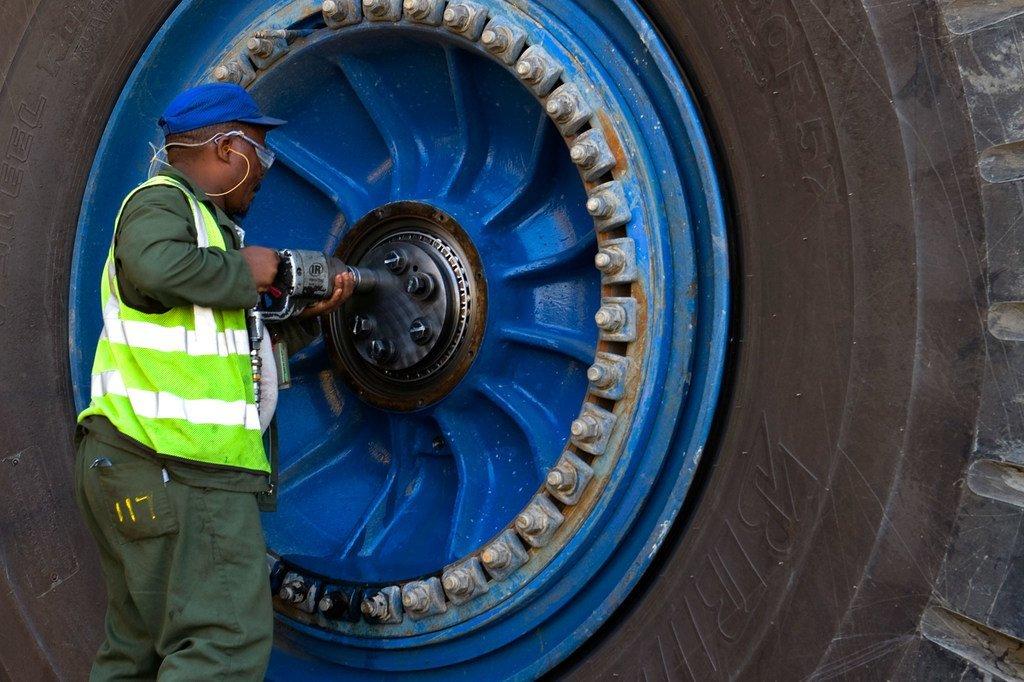 Un ouvrier portant un masque répare une roue d'un camion de transport géant dans une mine d'uranium en Namibie.