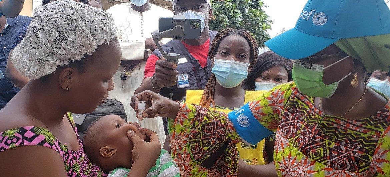 La Représentante de l'UNICEF au Bénin vaccine un enfant après que sa mère a accepté.