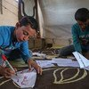 Two boys making paper masks at the Al-Tah IDP camp in Idlib Governorate, Syria.