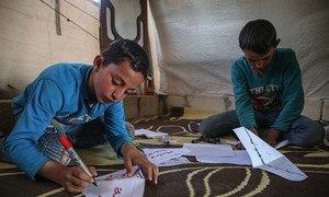 Dos niños fabrican mascarillas de papel en un campamento de refugiados en Siria.