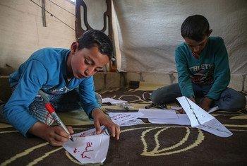 叙利亚伊德利卜的境内流离失所者营地内,两名男童正在制作纸口罩。