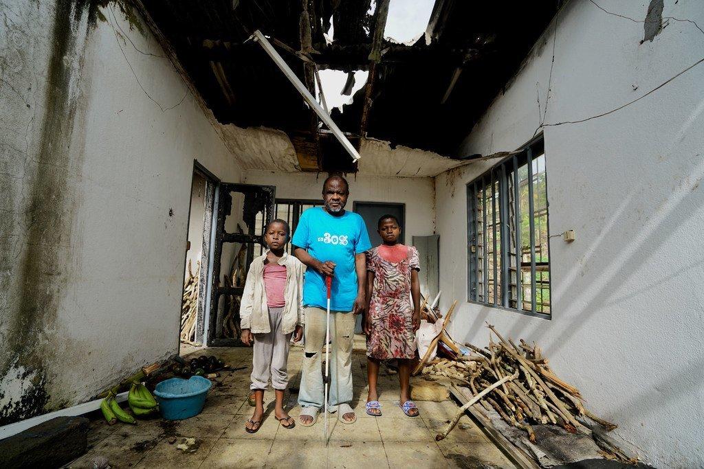 Ambuchu John, âgé de 58 ans, est complètement aveugle. Il pose dans sa « nouvelle » maison avec ses deux enfants aînés. Ils ont été déplacés par les combats dans le district de Buea, dans la région du Sud-Ouest, du Cameroun.
