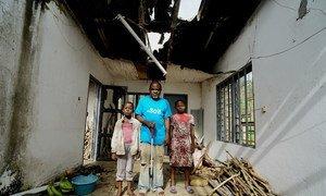 现年58岁、完全失明的安布楚·约翰和两个年长的孩子站在他们的新家前合影,他们由于喀麦隆的冲突而流离失所。