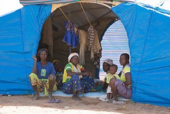 Family members who have fled conflict sit inside their tent at the Pissila camp for displaced people in Burkina Faso.
