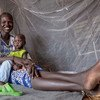 Une mère et son bébé de neuf mois sont assis sous une moustiquaire fournie par l'UNICEF dans l'État du Nil supérieur, au Soudan du Sud.