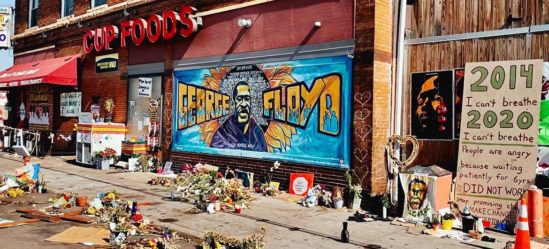 美国明尼苏达州,民众在佛洛依德遭警察跪压的事发地点绘制了纪念壁画并摆放了鲜花。
