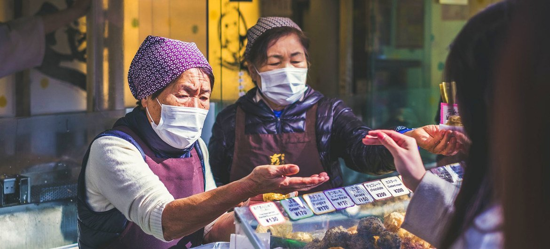 Vendors wear face masks at a food market in Japan.