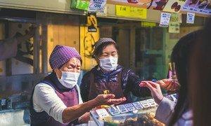 Des vendeuses portent des masques dans un marché au Japon.