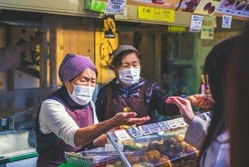 日本街头,一位店主戴着口罩售卖食品。
