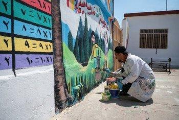 """عضو في فريق """"النقد مقابل العمل"""" الذي يدعمه برنامج الأمم المتحدة الإنمائي، يرسم لوحة جدارية في مدرسة للبنات غربي الموصل، في العراق."""