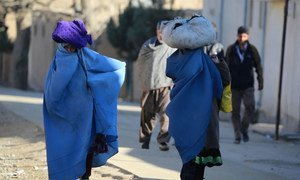 Women carry bundles through a neighbourhood of Kabul, the capital of Afghanistan.