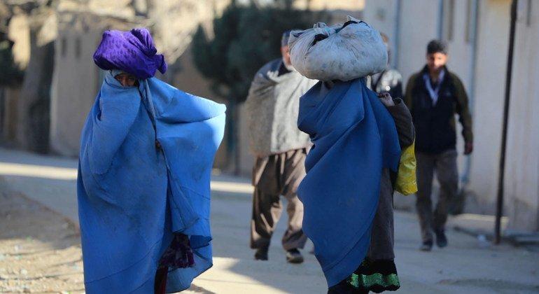 阿富汗首都喀布尔的一个街区,妇女背着包裹。