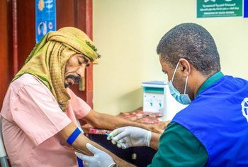A doctor treats a patient while wearing PPE to stop COVID-19 transmission in an IOM-supported health centre in Aden City, Yemen.