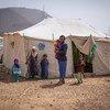 أب يقف مع أطفاله خارج خيمتهم في موقع للنازحين خارج مدينة مأرب باليمن.