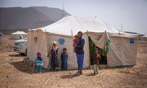 Un père avec ses enfants devant leur tente dans un site de déplacés près de Mareb, au Yémen.