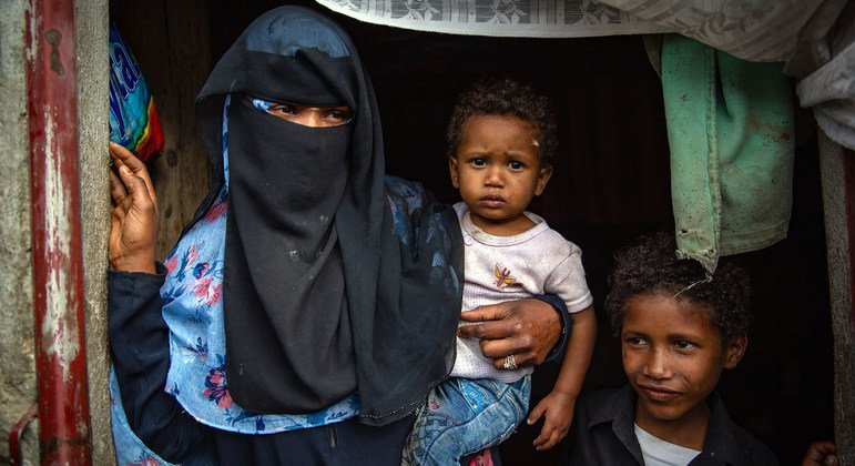 A displaced woman stands in the doorway of her shelter with her young children in Ibb city, Yemen.