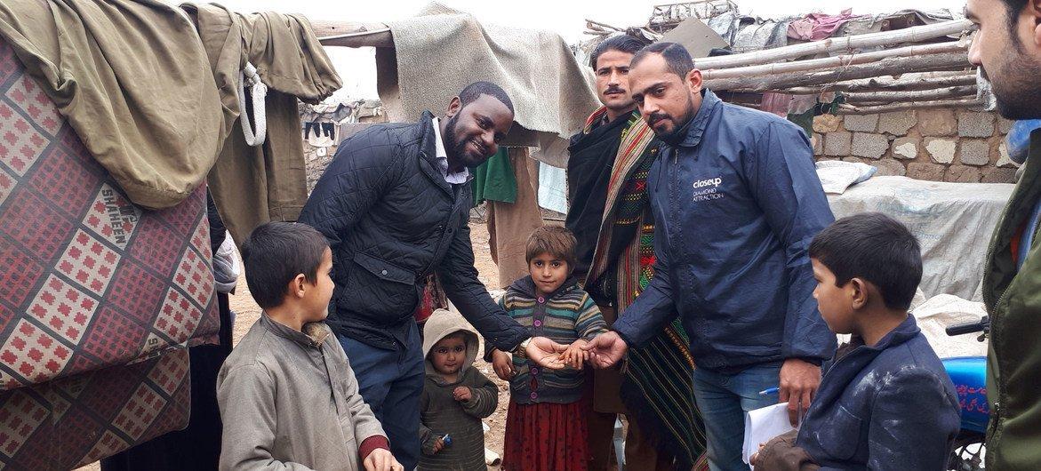 डेलिन चिमेन्या (बाएँ) पाकिस्तान में एक परिवार के साथ, जहाँ बच्चों को पोलियो की दवा पिलाई गई है.