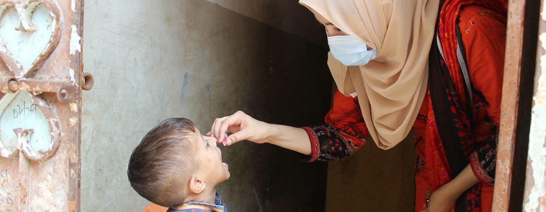 تقدم حسنة غول، العاملة في منظمة اليونيسف في باكستان، لقاح شلل الأطفال الفموي لطفل صغير.
