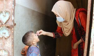 पाकिस्तान में यूनीसेफ़ की स्टाफ़ सदस्य हुसना गुल पोलियो टीकाकरण अभियान के तहत एक बच्चे को वैक्सीन पिलाते हुए.