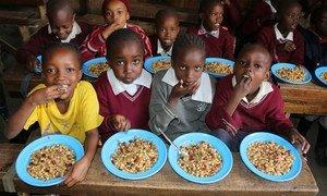 """Niños en Kenia disfrutan de un almuerzo hecho con vegetales que habrían sido tirados porque no tienen la forma estéticamente """"correcta"""" para ser exportados."""