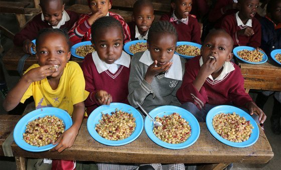 Kenyan school children enjoy a lunch made with unusually shaped vegetables which were deemed not good enough for export.