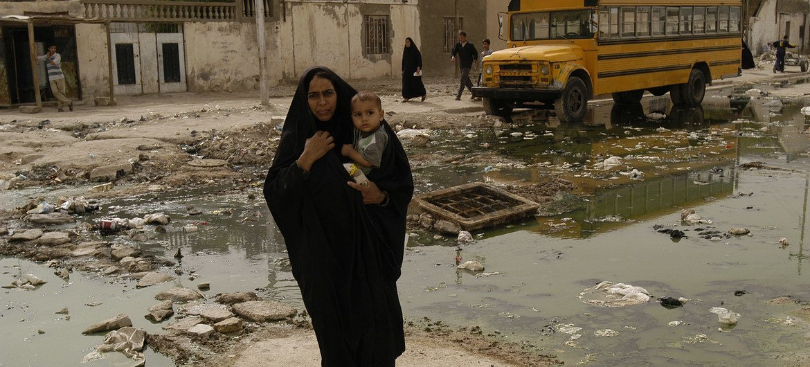 A woman carrying a toddler crosses a street in the southern Iraqi city of Basra. (file photo)