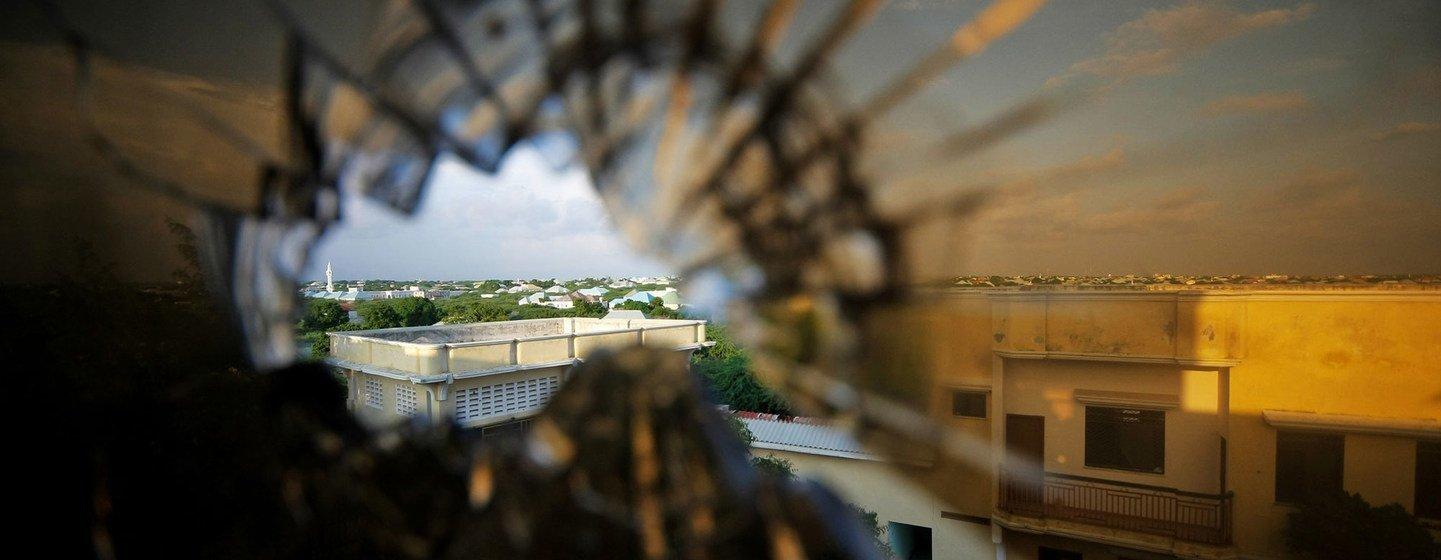 Vue de la banlieue nord de Mogadiscio, en Somalie, à travers la vitre d'un hôtel brisée par une balle.