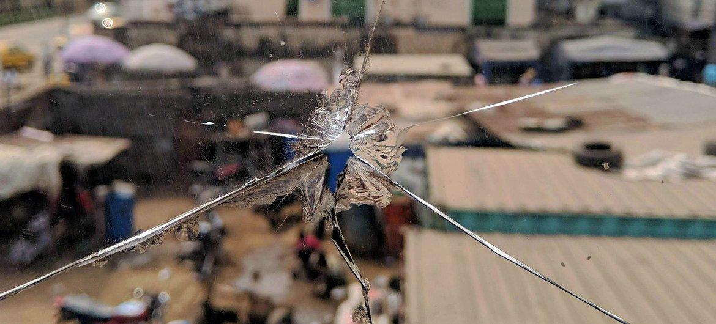 مشهد من مدينة لاغوس النيجيرية من خلال نافذة زجاجية مشروخة بفعل الرصاص.