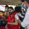 भारत के मध्य प्रदेश राज्य के झाबुआ ज़िले के एक टीकाकरण केंद्र पर एक महिला को कोविड-19 वैक्सीन की पहली ख़ुराक दी जा रही है.