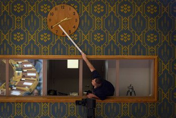一名联合国工作人员正在调整安理会会议厅内的时钟。(2019年11月图片)