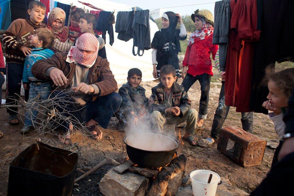 流离失所的叙利亚人在靠近土耳其边境的卡阿营地用明火做饭。(档案照片)