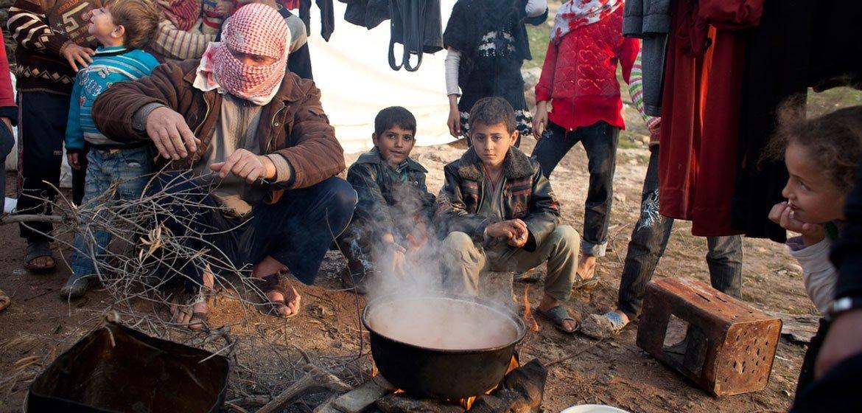 Sírios deslocados cozinham uma refeição no acampamento em Qah, perto da fronteira com a Turquia.