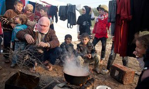 Displaced Syrians cook a meal on an open fire at Qah Camp, close to the Turkish border. (file)