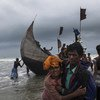 A man helps a woman to the shore, as a boat arrives with Rohingya refugees in Teknaf, Cox's Bazar, Bangladesh. (file photo)