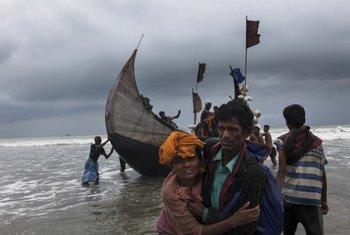 रोहिंज्या शरणार्थियों से भरी एक नाव, बांग्लादेश के टेकनाफ़ किनारे पर पहुँचने के बाद, एक व्यक्ति, एक महिला को किनारे तक पहुँचने में मदद करता हुआ. (फ़ाइल फ़ोटो)