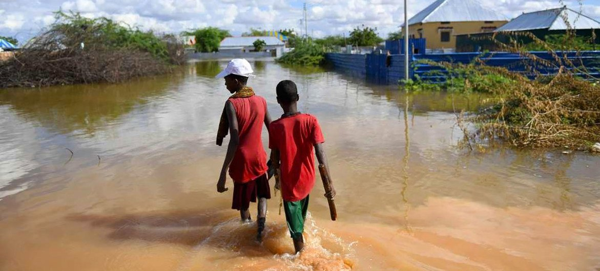 Young boys walk through a section of a flooded residential area in Belet Weyne, Somalia.