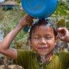 Una niña se lava la cara en una instalación de agua recién abiera en Camboya.