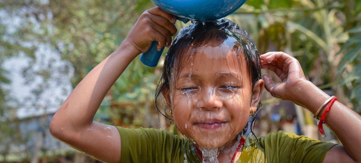 一名柬埔寨儿童在家中新安装的水龙头前洗脸。
