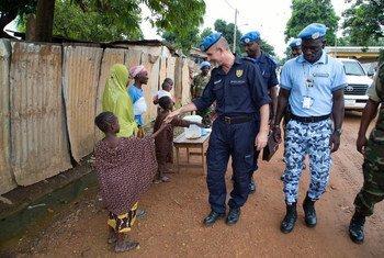 Conselheiro da Polícia da ONU, Luis Carrilho, cumprimenta uma criança durante sua patrulha a pé pelas ruas de Bangui