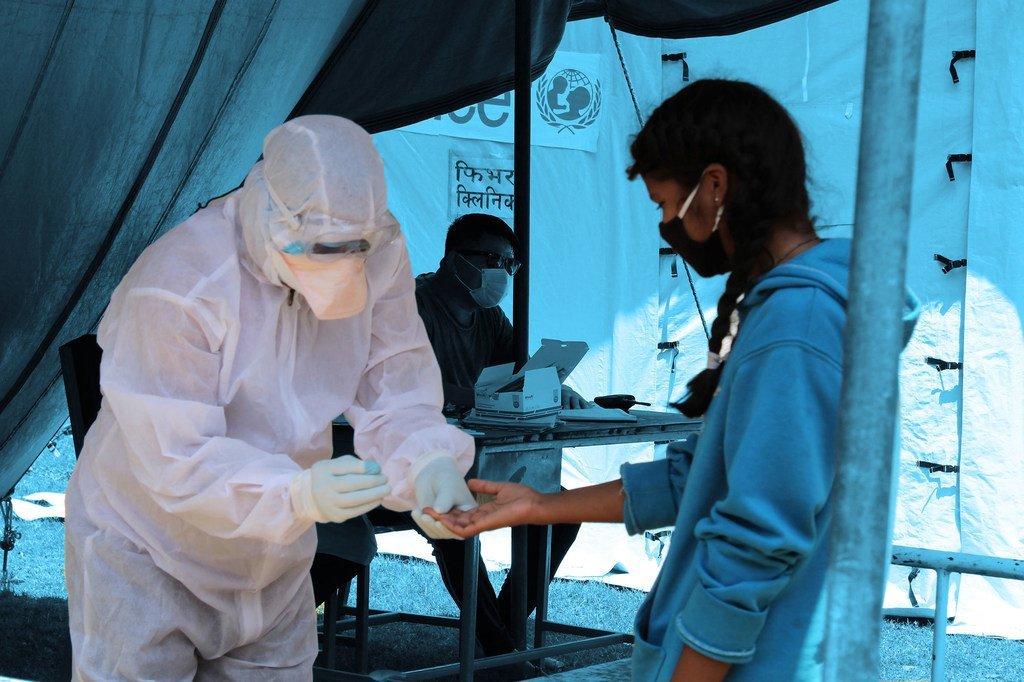 Un agent de santé effectue un dépistage de la Covid-19 chez une jeune fille dans une clinique installée à côté d'un hôpital du district de Saptari, au Népal.