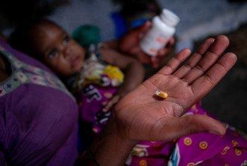 Mãe em Mbarara, no Uganda, dando medicamento contra HIV a seus filhos