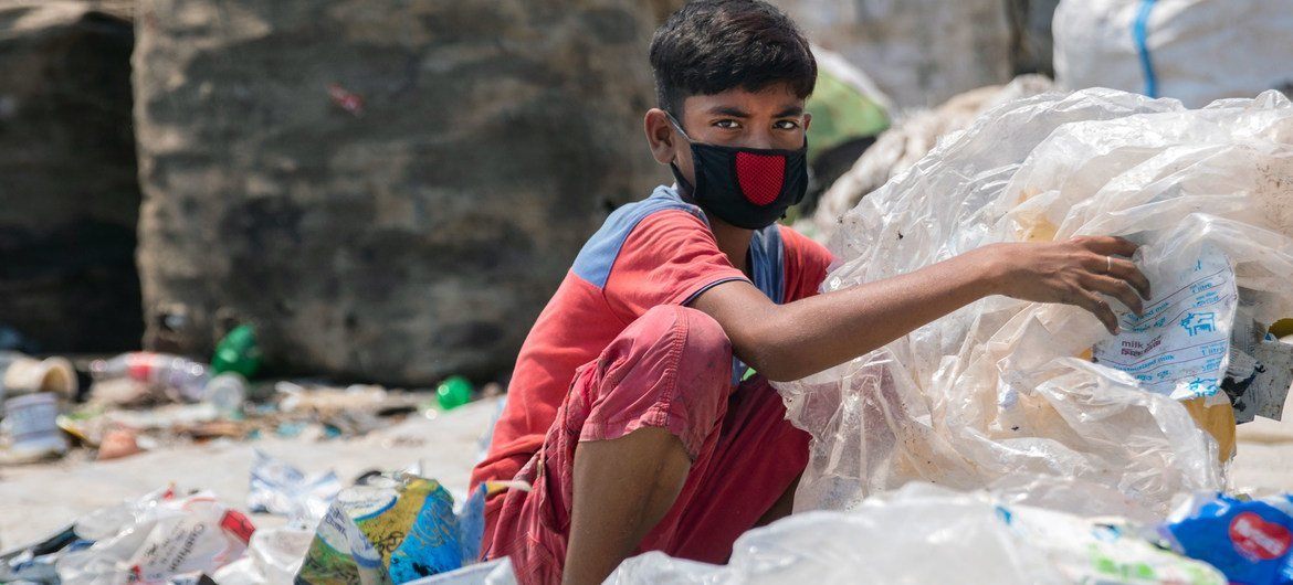 Twelve-year-old boy in Dhaka, capital of Bangladesh, sorts through hazardous plastic waste without any protection, working to support his family amidst the lockdown.