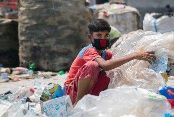 Kijana wa miaka 12 nchini Bangladesh akichambua taka za plastiki bila kuwa na kinga yoyote, na hiyo ni kazi yake inayomuwezesha kusaidia familia yake