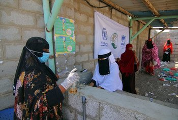Women queue at a distribution point in Kharaz Camp, Yemen, where measures are being taken to protect beneficiaries and staff against COVID-19.