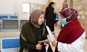 在耶路撒冷卫生中心,一名卫生工作者正在向患者提供与2019冠状病毒病有关的信息。